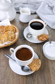Eine tasse kaffee mit glutenfreien keksen aus getreide auf dem couchtisch. es ist zeit, einen happen zu essen