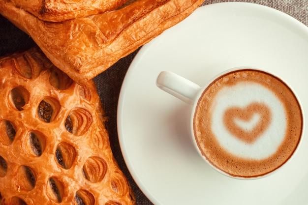 Eine tasse kaffee mit herz und kuchen.