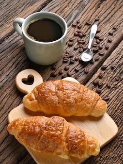 Eine tasse kaffee mit kaffeebohnen und croissant auf holztisch