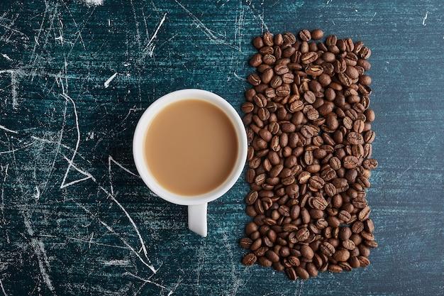 Eine tasse kaffee mit körnern auf blauer oberfläche.