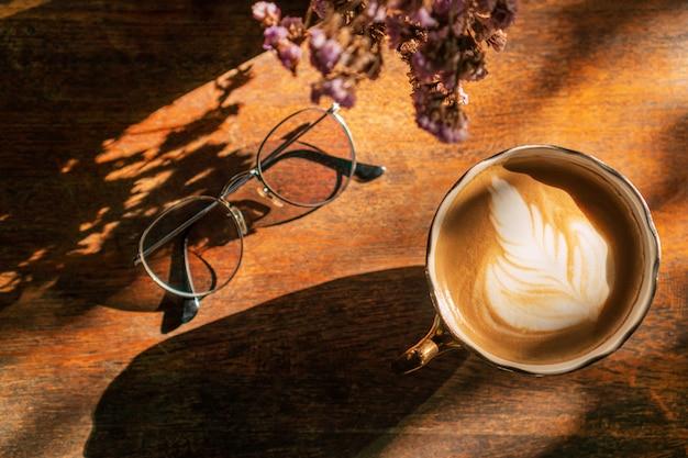 Eine tasse kaffee mit latte art und gläsern auf holztisch im café, draufsicht.