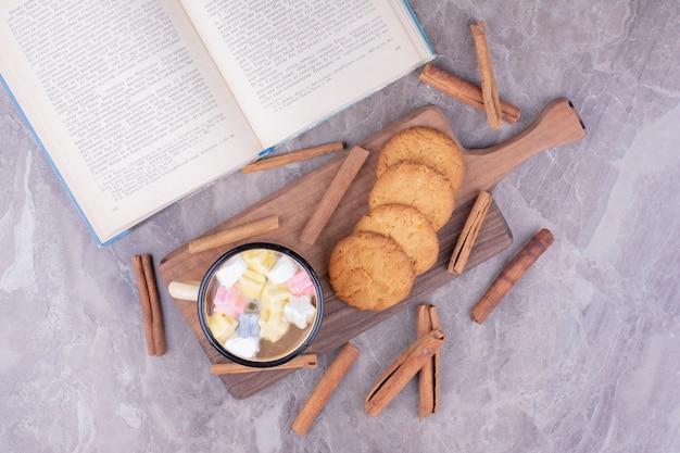 Eine tasse kaffee mit marshmallow und keksen auf holzbrett.