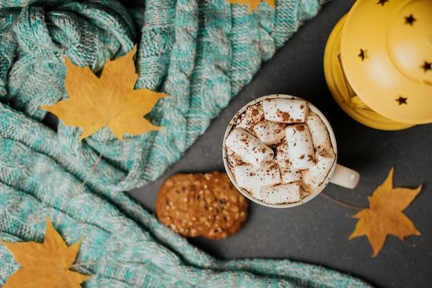 Eine tasse kaffee mit marshmallows, keksen, einem blauen strickplaid und gelbem herbstlaub auf dunkelgrau