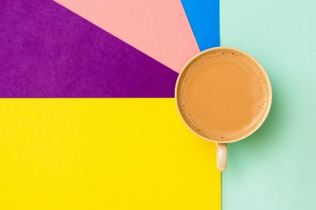 Eine tasse kaffee mit milch auf einem bunten hintergrund. der blick von oben. flach liegen.