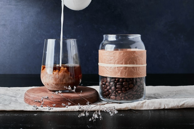 Eine tasse kaffee mit milch auf einem holzbrett mit bohnen im glas.