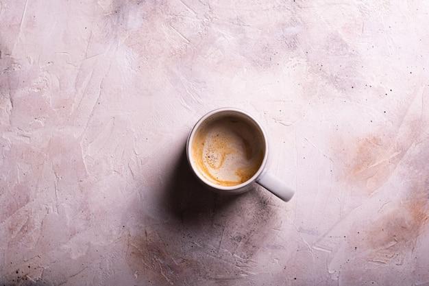 Eine tasse kaffee mit milch flach lag auf einem hellen hintergrund nah oben