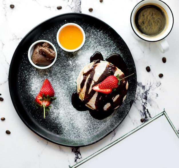Eine tasse kaffee mit pfannkuchen in schokolade