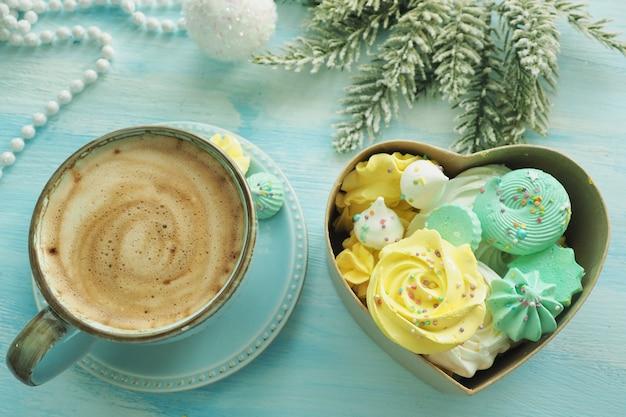 Eine tasse kaffee mit schaum, eine herzförmige schachtel mit baisers in verschiedenen farben, eine weihnachtskugel und ein tannenzweig.