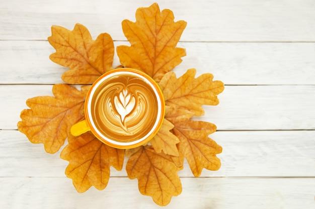 Eine tasse kaffee mit schaum steht auf herbstlichen gelben eichenblättern auf weißem hintergrund, ansicht von oben. flach liegen.