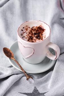 Eine tasse kaffee mit schokolade auf decke im bett haben