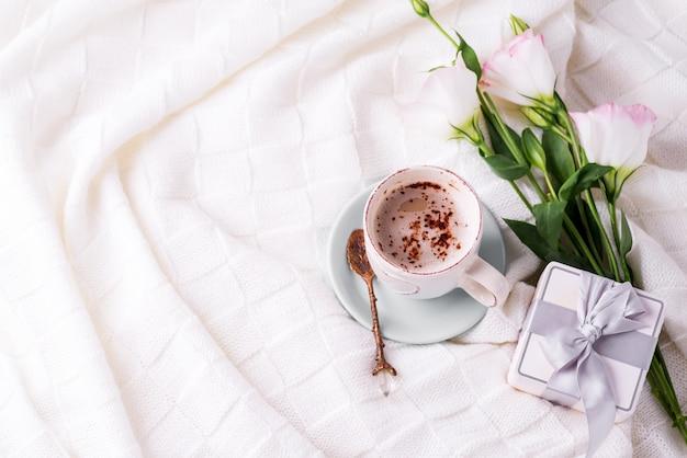 Eine tasse kaffee mit schokolade, blumen eustoma und geschenkbox auf decke im bett trinken.