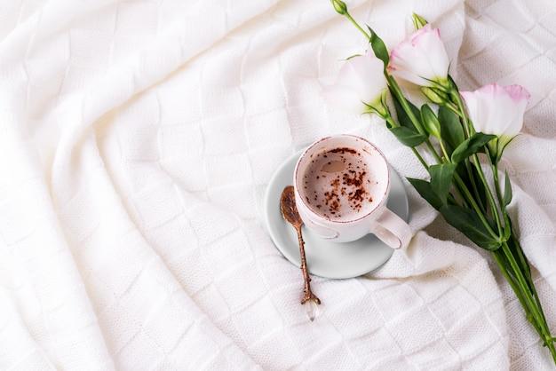 Eine tasse kaffee mit schokolade trinken, blüht eustoma auf decke im bett.