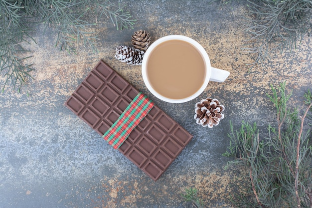 Eine tasse kaffee mit tannenzapfen und schokolade. foto in hoher qualität
