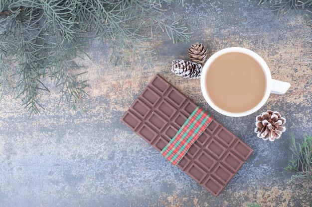 Eine tasse kaffee mit tannenzapfen und schokolade