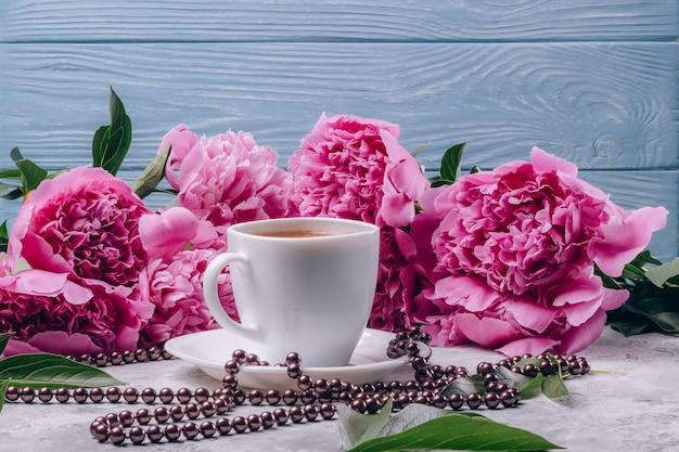 Eine tasse kaffee mit üppigen rosa pfingstrosen