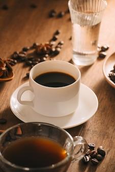 Eine tasse kaffee mit wasser, kaffeebohnen und tee auf holzoberfläche