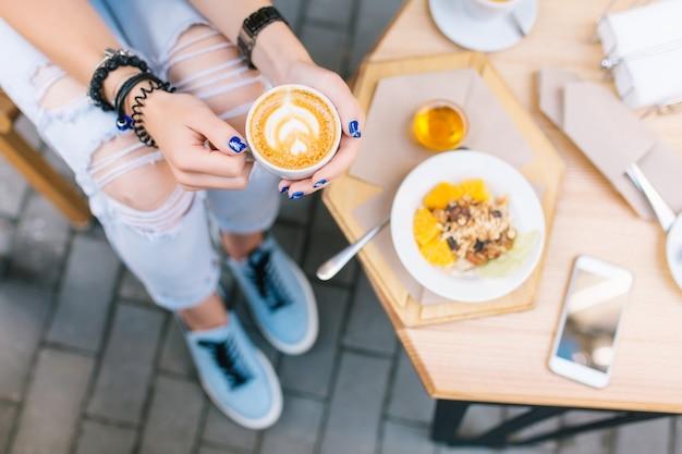 Eine tasse kaffee mit zeichnung in den händen der jungen frau, die an der terrasse sitzt