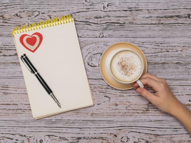 Eine tasse kaffee mit zimt und milch und ein notizbuch auf einem holztisch