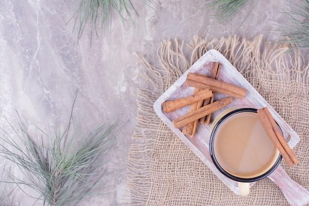 Eine tasse kaffee mit zimtgeschmack auf einem holzbrett