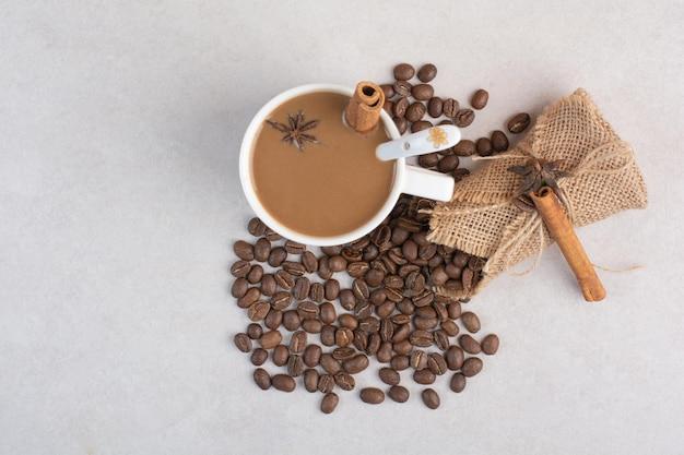 Eine tasse kaffee mit zimtstangen und kaffeebohnen auf marmorhintergrund. foto in hoher qualität