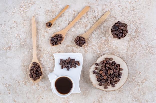 Eine tasse kaffee neben mehreren kleinen bündeln kaffeebohnen