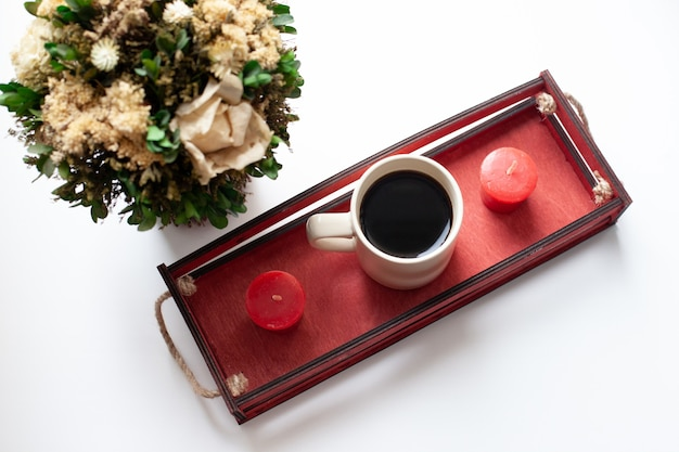 Eine tasse kaffee oder tee, trockene blumen und weiße, rote kerzen, eine rote holzkiste am fenster.