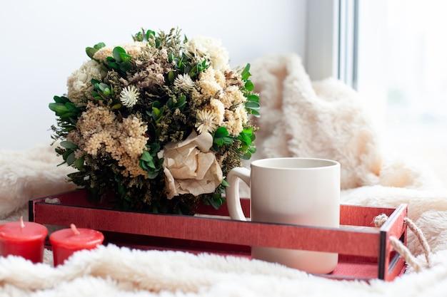 Eine tasse kaffee oder tee, trockene blumen und weiße, rote kerzen, eine rote holzkiste auf einer beigen decke.