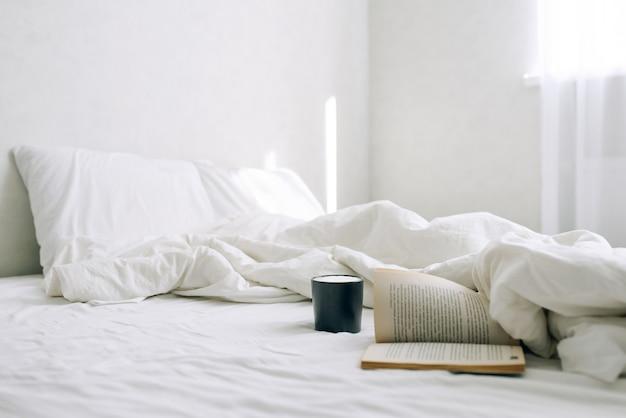 Eine tasse kaffee oder tee und ein offenes buch auf dem bett im hellen morgenschlafzimmer