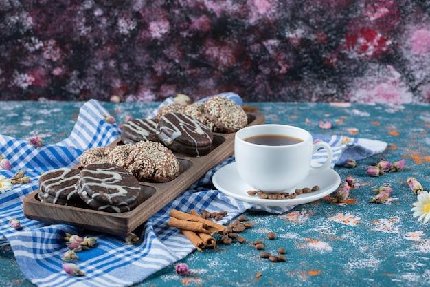 Eine tasse kaffee serviert mit schokoladenkeksen.