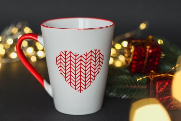 Eine tasse kaffee steht auf dem hintergrund der weihnachtsbeleuchtung.