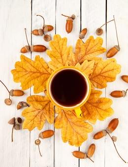 Eine tasse kaffee steht auf herbstgelben eichenblättern mit eicheln auf weißem hintergrund ansicht von oben