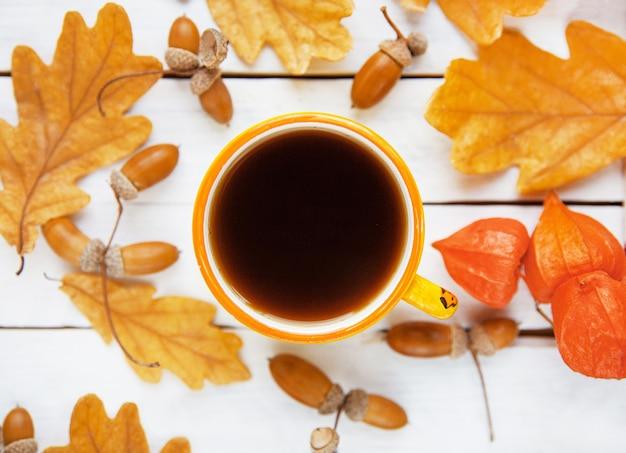 Eine tasse kaffee steht auf herbstgelben eichenblättern mit eicheln auf weißem hintergrund