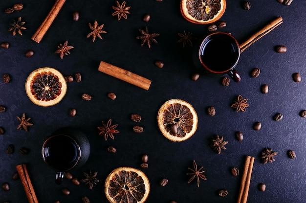 Eine tasse kaffee, sternanis, zimt, getrocknete orange und kaffeebohnen auf einer dunklen küchenarbeitsplatte