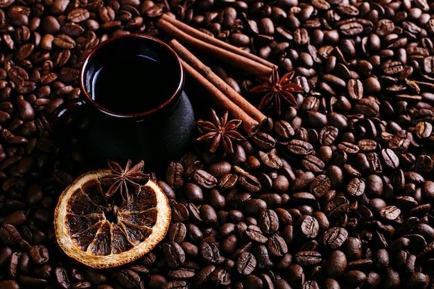Eine tasse kaffee, sternanis, zimt und getrocknete orange auf kaffeebohnen
