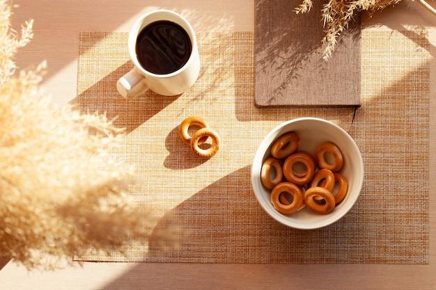 Eine tasse kaffee, trockene blumen, barankis, notizblock auf holztisch. braun und weiß.