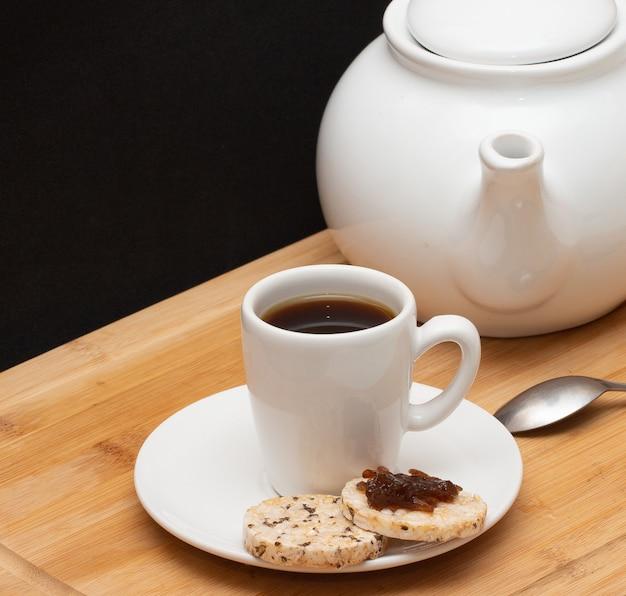 Eine tasse kaffee, umgeben von einer kaffeekanne