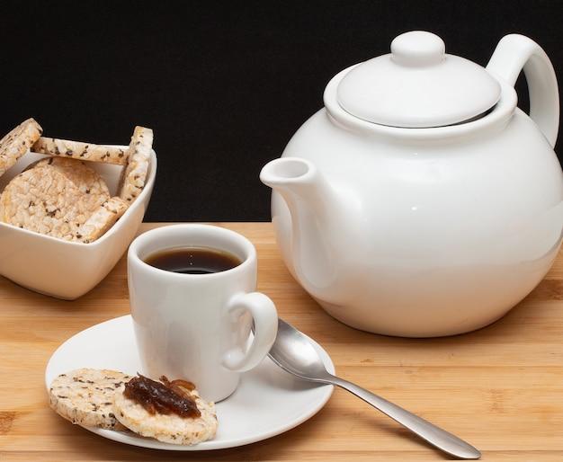 Eine tasse kaffee, umgeben von einer schüssel voller reiskekse und einer kaffeekanne