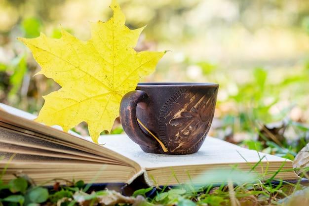 Eine tasse kaffee und ahornblatt auf einem offenen buch im herbstwald. bücher in der natur lesen