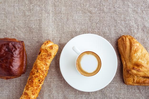 Eine tasse kaffee und brötchen standen in einer reihe. draufsicht flachen stil