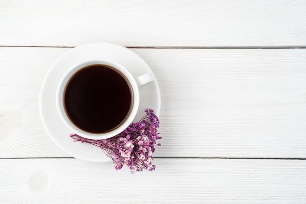 Eine tasse kaffee und ein blumenstrauß auf einem weißen hintergrund. draufsicht mit platz zum kopieren.