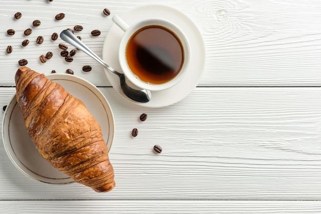 Eine tasse kaffee und ein croissant auf einem weißen tisch mit kopierraum. flache zusammensetzung mit kaffee und croissant. leichtes frühstückskonzept.