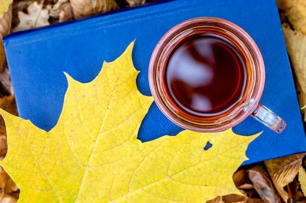 Eine tasse kaffee und ein gelbes ahornblatt auf einem buch im herbstwald