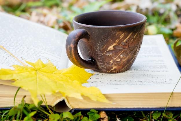 Eine tasse kaffee und ein gelbes ahornblatt auf einem buch im wald