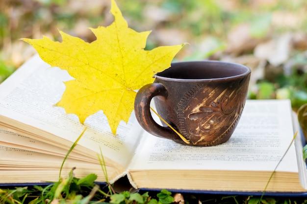 Eine tasse kaffee und ein gelbes ahornblatt auf einem offenen buch im wald