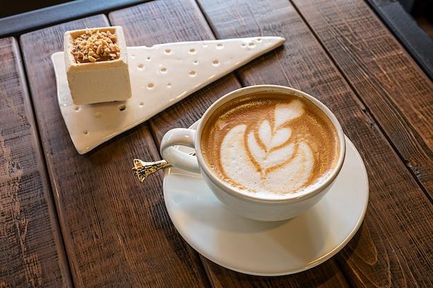 Eine tasse kaffee und ein kuchen auf einem holztisch in einem café