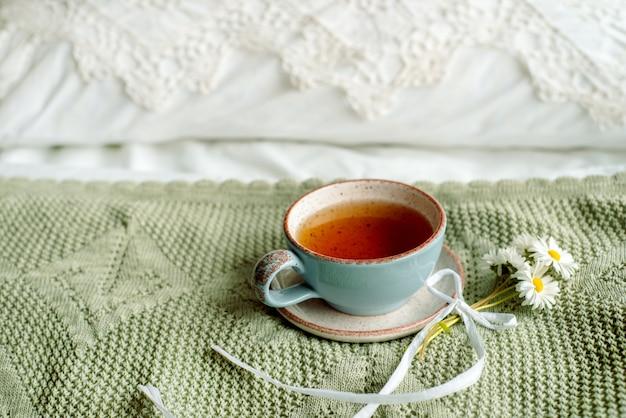 Eine tasse kaffee und ein offenes buch auf einem weißen offenen bett. frühstück. heller gemütlicher tag.