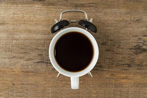 Eine tasse kaffee und ein schwarzer vintage-wecker auf einem hölzernen hintergrund
