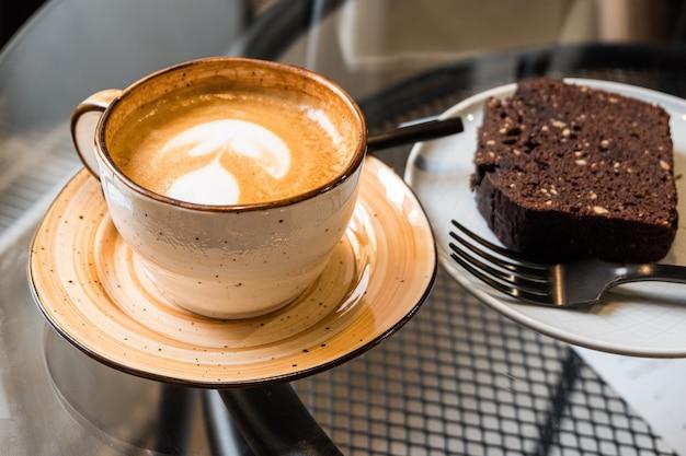 Eine tasse kaffee und ein stück schokoladenkuchen auf einem glastisch