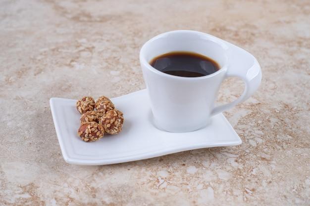 Eine tasse kaffee und glasierte erdnüsse auf einer platte
