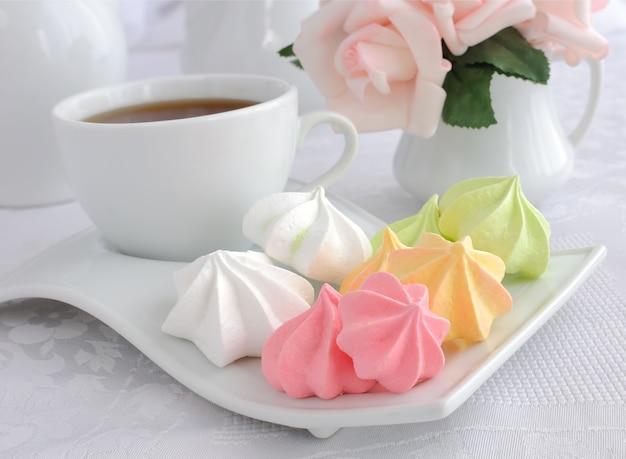 Eine tasse kaffee und kekse baiser auf einem teller nahaufnahme